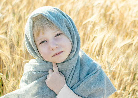 poquito: little girl dressed in gray kerchief lin wheat field in summer. Close-up bit sad 5 years old child