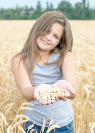 Wheat grains in the palms of a beautiful little girl. Symbol of life, peace, growth. Focus on palms of hands