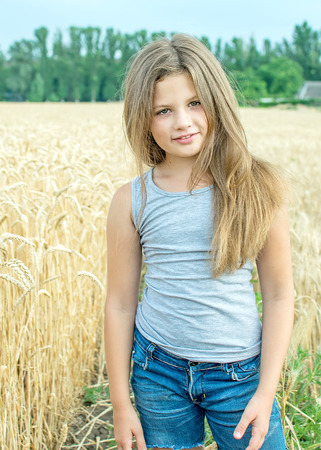 adorable little girl with long heir Posing in golden wheat field at a summer day Stock Photo