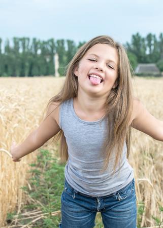 Spielerisches kleines Mädchen zeigt ihre Zunge im Weizenfeld an einem Sommertag Standard-Bild - 82331660