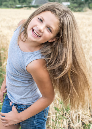 sexy little girl playing with her long hair posing in wheat field at a summer day Stock Photo