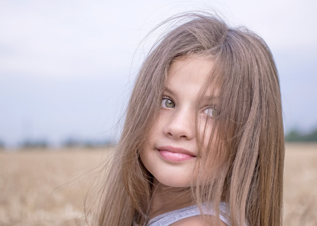 Little girl in golden wheat field in summer day. Portrait of a beautiful child. Concept of purity, growth, happiness Фото со стока