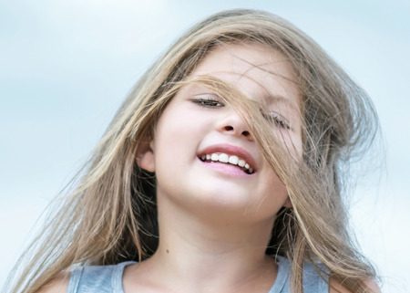 Little beautiful happy girl with hair fluttering in the wind. Portrait of a smiling child on blue sky backgroung
