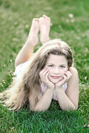 Klein mooi meisje met lang los haar op groen gras op zomerdag