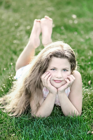 little beautiful girl with long loose hair on green grass at summer day