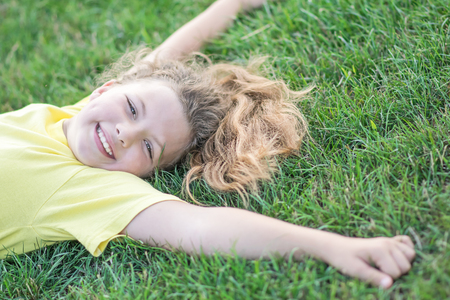 Happy pretty girl lying on green grass with outstretched arms and smiling at summer Stock Photo