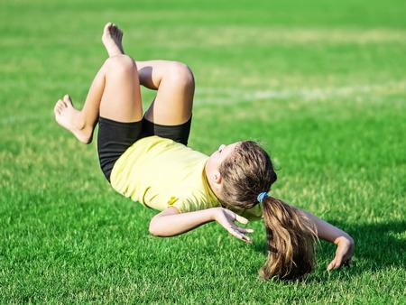 Petite fille faisant du somersault et perd le solde