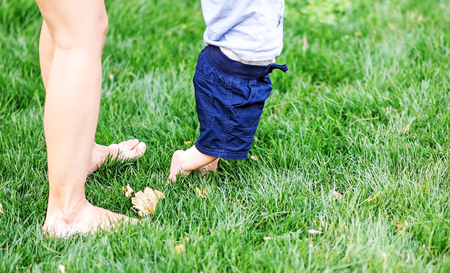 Little child doing First steps on green grass. Legs of young mother and her baby son