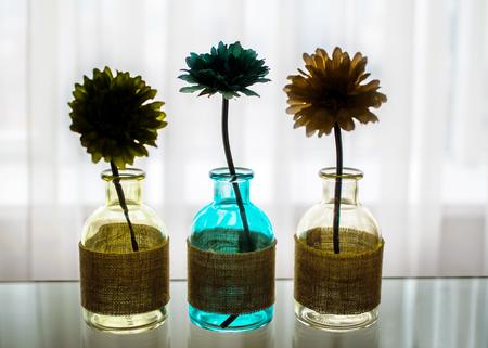 窓透明の白いカーテンが付いているテーブルの色付きのガラス瓶の家の装飾の花のシルエット。ぼやけた背景 写真素材