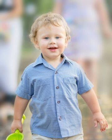 A happy smiling baby boy playing at summer park. A walking family with a cute little son outside. Outsides, walk, portrait, joy, happiness, beautiful kid