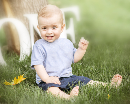 A portrait of a happy cute baby boy sitting on green grass outdoor at summer day. Emotions, smile, grimace, surprise, delight, kid, toddler