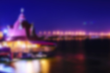 Beautiful blurred night Dnipro city view. Dark bue sky, river and building with lights or illuminations background.