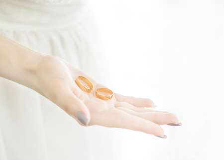 Close-up young brides hand holding two golden wedding rings on open palm. Wedding tradition and symbol. White background with soft light