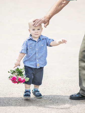 Portrait of small baby boy walking with pink roses bouquet outdoor and grandfathers hand stroking his head.