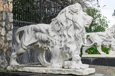 City sculptures of the two white lions and a lion cub at the entrance. Local landmark. Foto de archivo