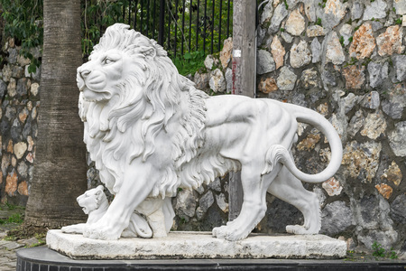City sculpture of a lion and a lion cub at the entrance. Local landmark. Side view. Фото со стока