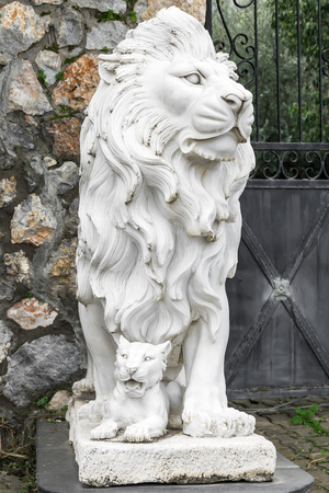 City sculpture of a lion and a lion cub at the entrance. Local landmark. Front view. Stock Photo