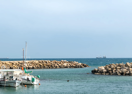 Seascape with rocky beach. Sea pier with boats and yachts.