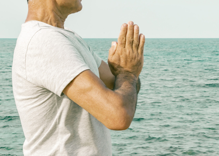 An adult man standing with palms in a gesture namaste by the sea. The concept of spirituality and self-awareness. Stock fotó