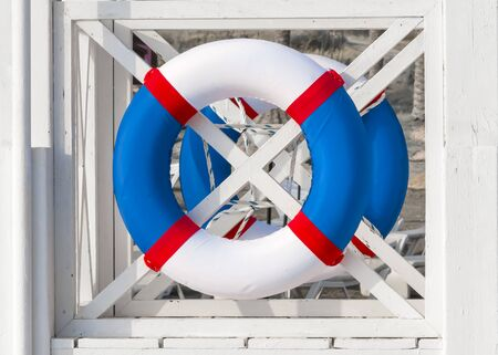 Close-up white wooden lifeguard with blue red colors lifebuoy Фото со стока