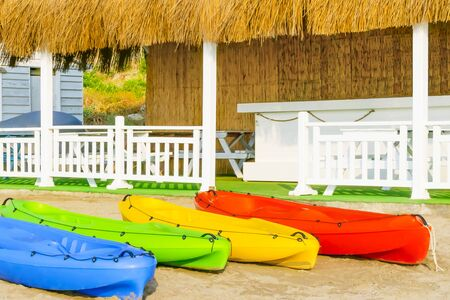 Colorful kayaks on white sand on the beach of Cyprus against summer house with white wooden fence and reed roof