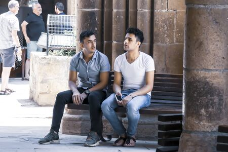 CYPRUS, NICOSIA - JUNE 10, 2019: Two handsome guys sitting together on wooden bench next to ancient columns of the historic building Selimiye Mosque.