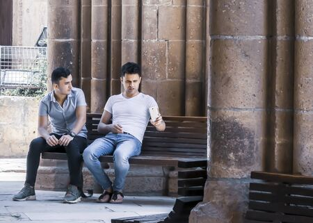 CYPRUS, NICOSIA - JUNE 10, 2019: Two men sitting and talking together on a bench next to ancient columns of the historic building Selimiye Mosque. One young man holding a smartphone