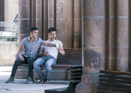CYPRUS, NICOSIA - JUNE 10, 2019: Two male sitting and talking together on a bench near the ancient columns of the historic building Selimiye Mosque. One young man holding a smartphone Éditoriale