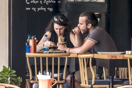 CYPRUS, NICOSIA - JUNE 10, 2019: Young couple eating in street outdoor restaurant. Man and woman enjoying fast food Éditoriale