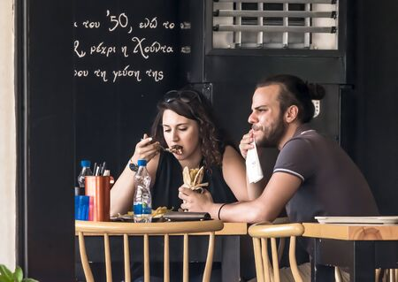 CYPRUS, NICOSIA - JUNE 10, 2019: Young couple eating in street outdoor restaurant. People enjoying fast food in cafe