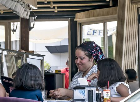 CYPRUS, NICOSIA - JUNE 10, 2019: Young smiling mother in traditional clothes enjoy a meal with two little daughters in open summer city cafe. Eating family