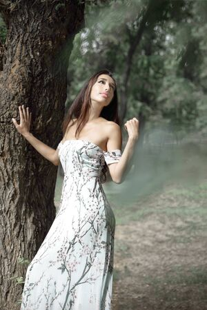 Young beautiful romantic smiling female with long dark hair posing standing next to big tree and looking up.