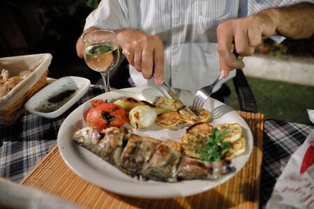 Dinner at the restaurant. Mediterranean food. Grilled fish and vegetables on a plate. Hands of a man cutting fish in a plate Фото со стока