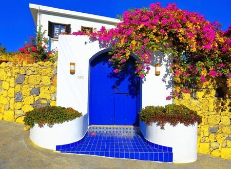 Traditional Mediterranean house with a stone fence and a large blue door decorated with flowering plants.
