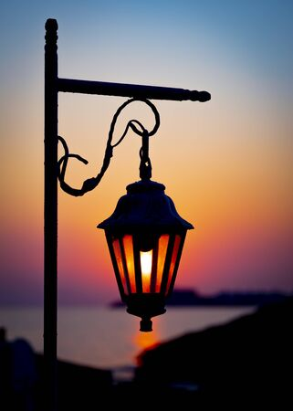 The magic light of the rising sun through the glass of a decorative lantern. Morning seascape