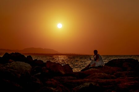 Silhouette of a young woman sitting on a stone beach and using a smartphone on a beautiful sea sunset background