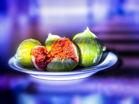 Fresh ripe figs on a plate on bright purple neon background. Фото со стока
