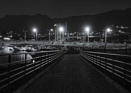 Pedestrian wooden bridge along the sea coast monochrome night background.