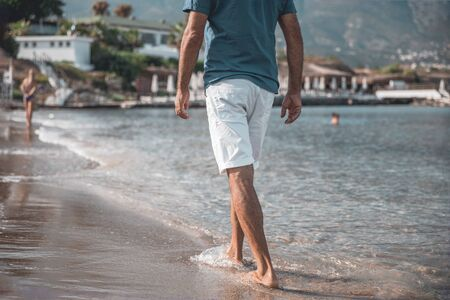 Adult handsome man walking barefoot on the water along the seashore. Famous North Cyprus Beach Background