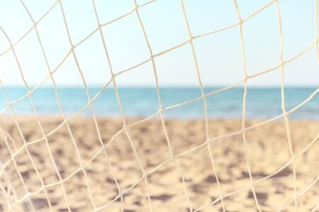 Soccer goal net on summer beach background. Focus on the grid on the background of blurry sandy shore.
