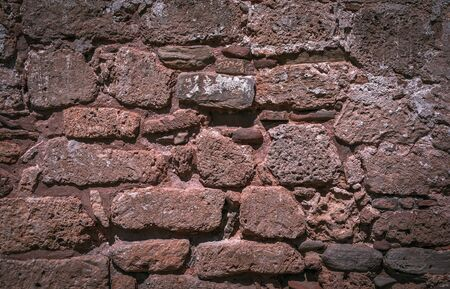 Dark brown stone wall of historical building background