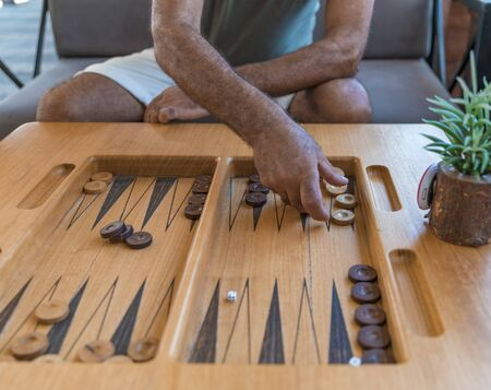 Male playing a traditional oriental board game of backgammon. Mens hands moving chips