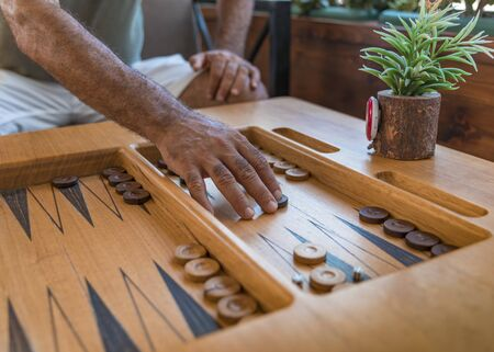 Male playing a traditional oriental board game of backgammon in coffee room. Mens hands moving chips Reklamní fotografie
