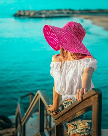 Young girl in a bright red hat with a closed face standing on a bridge by the sea and looking into the distance Reklamní fotografie