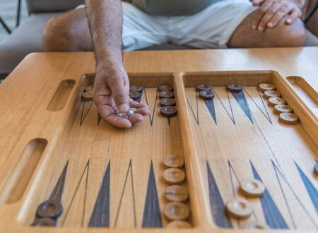 A man playing a traditional oriental board game of backgammon. Mens hands throwing dice Reklamní fotografie
