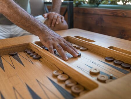 Male playing a traditional oriental board game of backgammon. Mens hands moving chips Reklamní fotografie