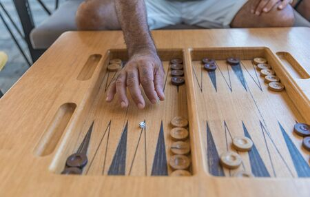 Male playing a traditional oriental board game of backgammon. Close-up mens hands throwing dice
