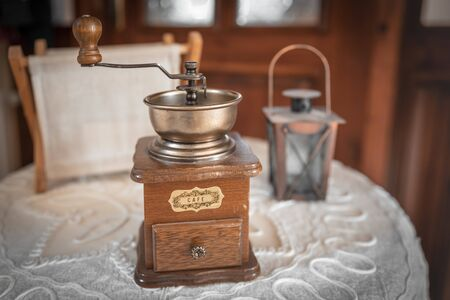 Vintage wooden manual coffee grinder, small decorative lantern and a newsstand on a round table with a white embroidered tablecloth