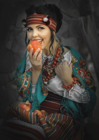 A pretty smiling young woman dressed in a Ukrainian folk costume sitting and eating apple. Cosplay