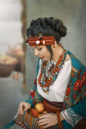 A pretty young female dressed in a Ukrainian folk costume sitting and holding apples. Cosplay